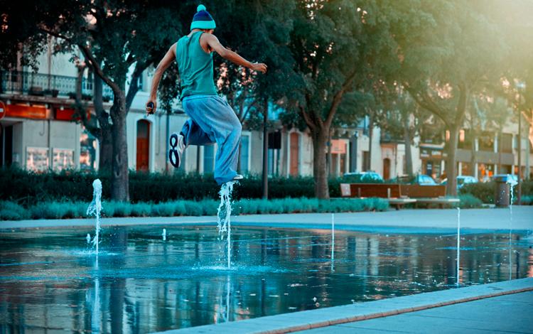 Chico salta sobre una fuente