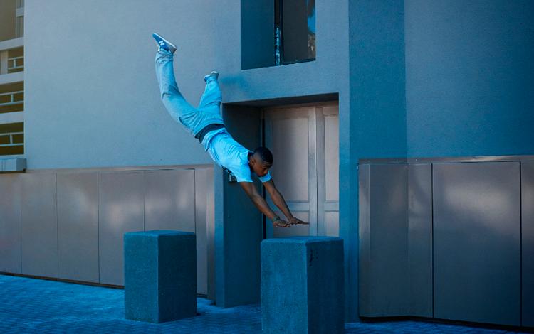 Chico salta en la puerta de un edificio