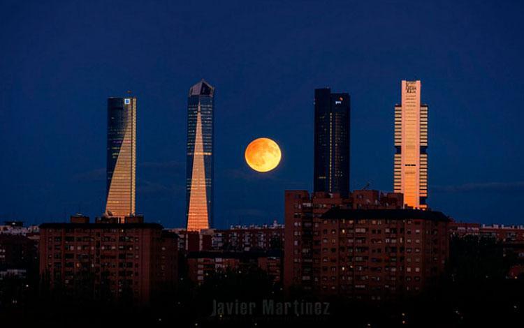 Luna llena con eclipse penumbral entre las cuatro torres del Skyline de Madrid