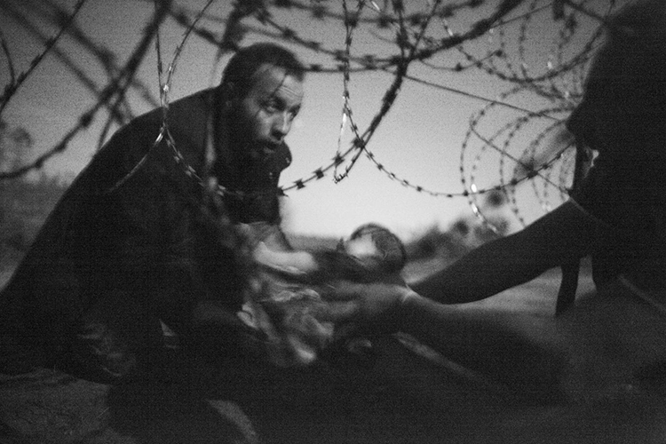 Warren Richardson, ganador en 2016 con una fotografía sobre la tragedia de los refugiados que muestra un hombre a traves de una vaya de pincho