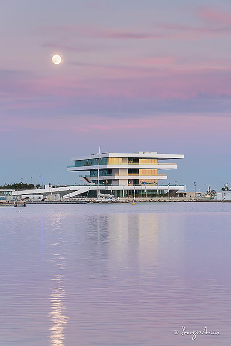 Luna encima del mar con edificio