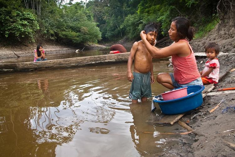 Mujer lava a su hijo en el río de Perú