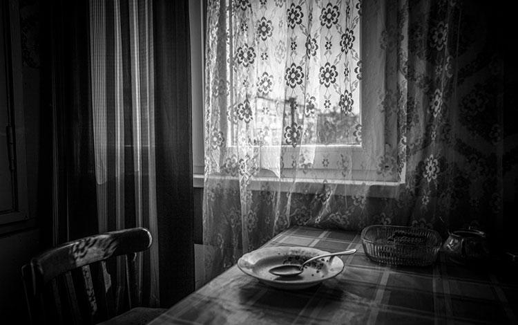plato vacío encima de la mesa al lado de una ventana