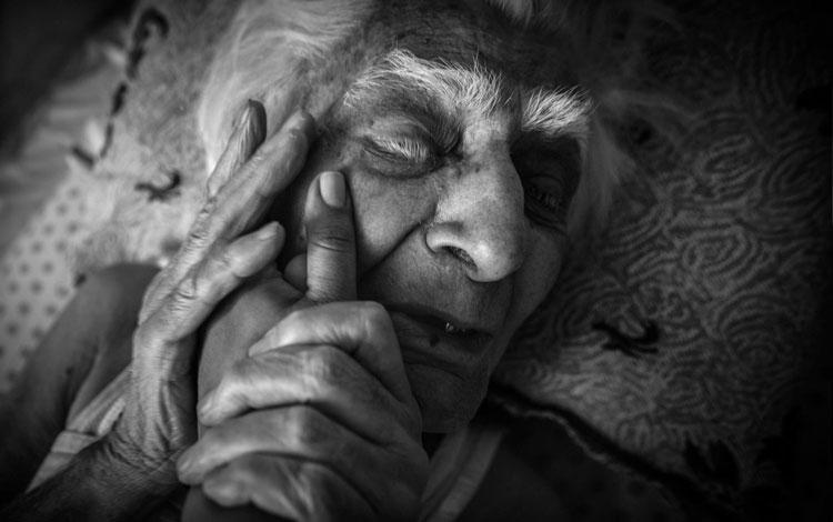 Abuela agarrando una mano contra la cara