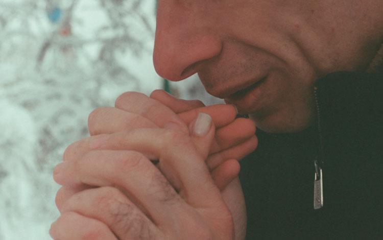 Boca de un hombre acercándose unas manos