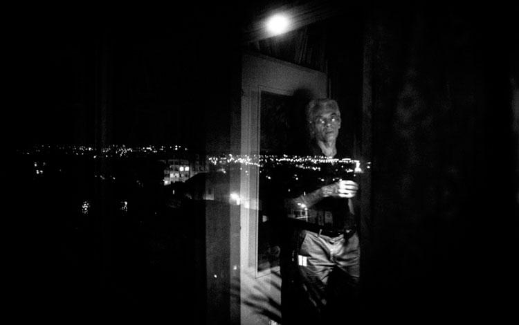 Hombre en el reflejo de una ventana que da a la ciudad