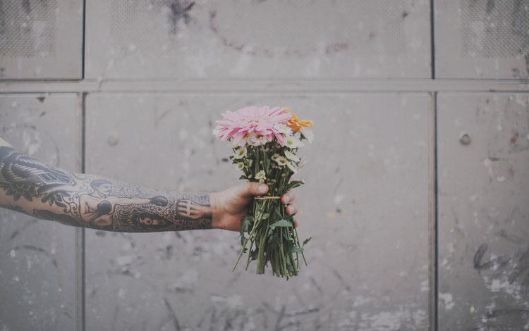 Ramo de flores sostenido por una mano con tatuajes