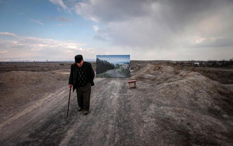 Hombre mayor en el campo con pintura de fondo