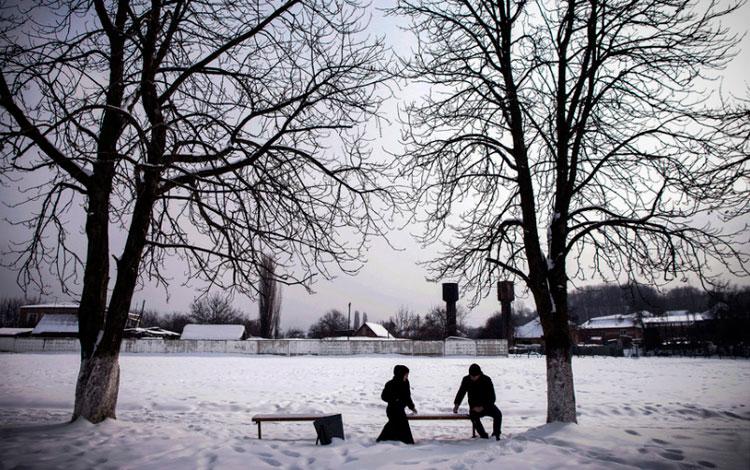 Pareja de musulmanes sentados en un banco con nieve