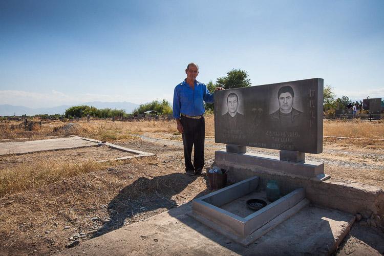 hombre junto a las lápidas de familiares