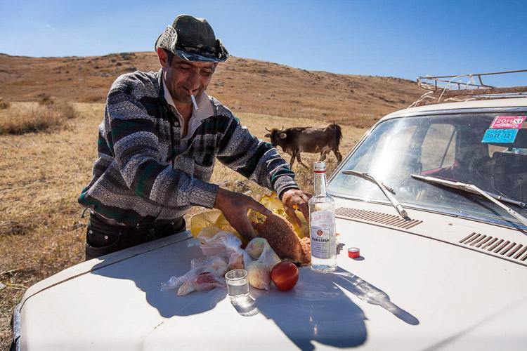 Hombre armenio comiendo en un coche
