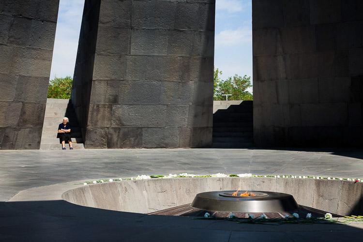 Mujer armenia sentada frente a monumento