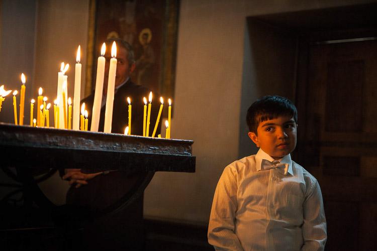 niño armenio dentro de una iglesia con velas