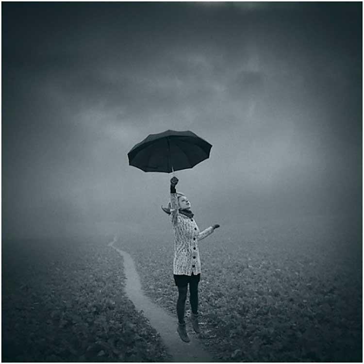 Chica saltando con un paraguas