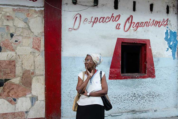 Cubana delante del despacho de osganismos