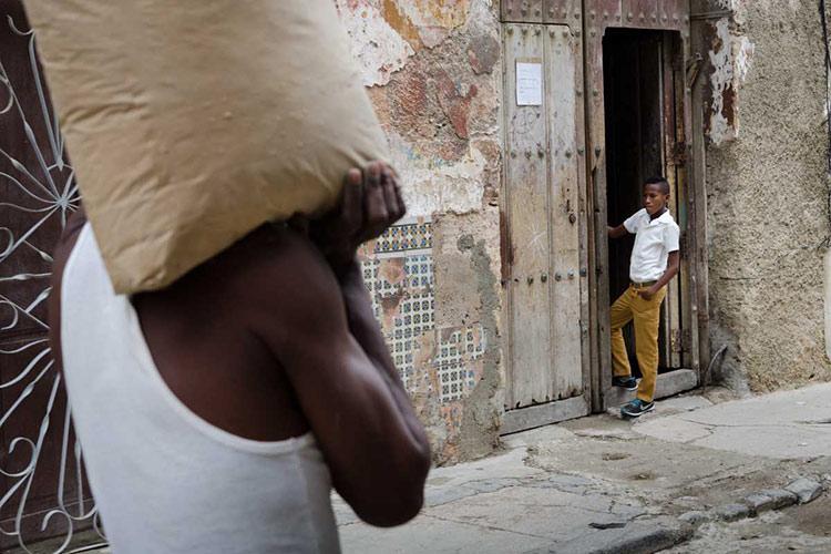 Hombre llevando un saco por las calles de la Habana