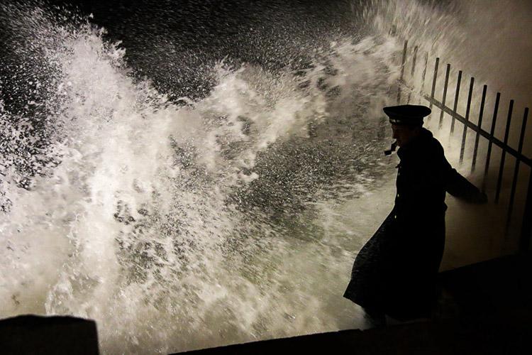 Un marinero bajando una gorra sin pico al mar, apenas puede dar algunos pasos a través de las olas que pueden derribarlo en cualquier momento. El agua helada envía escalofríos por su espina dorsal.