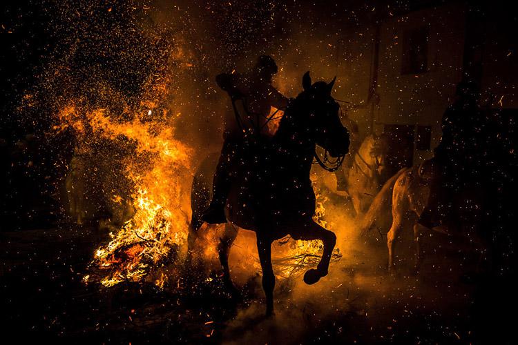 """Mención Especial del jurado (My Country) 2016: Las Luminarias por Luis Tato (España). Un hombre monta un caballo a través de la hoguera durante """"Las Luminarias"""", un ritual en honor de San Antonio, el patrón de los animales. La tradición, que tiene cientos de años, está destinada a purificar y proteger al animal para el próximo año."""