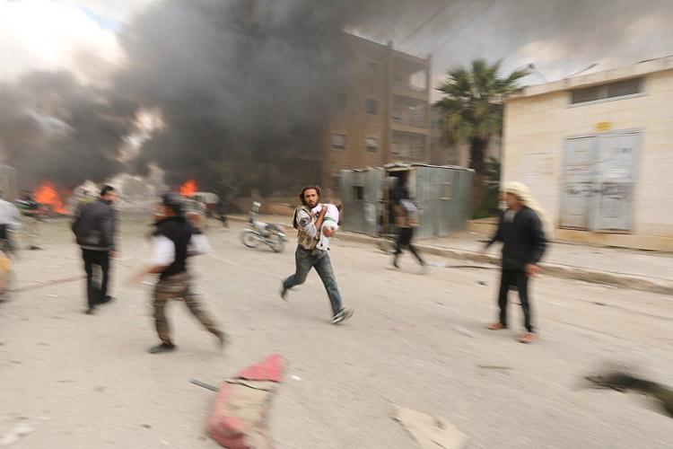 Hombre llevando a un niño durante el bombardeo por las fuerzas gubernamentales en Idlib, Siria, después de que los rebeldes tomaron el control.