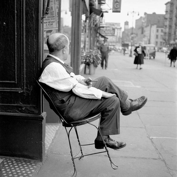 Señor sentado en una silla en la calle