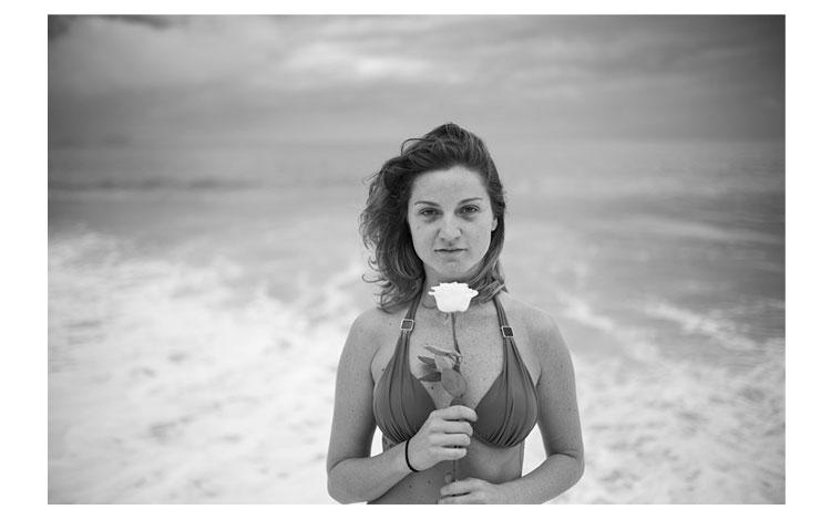 Chica sujetando una flor en las playas brasileñas