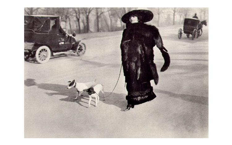 mujer pasea a su perro por una calle de París