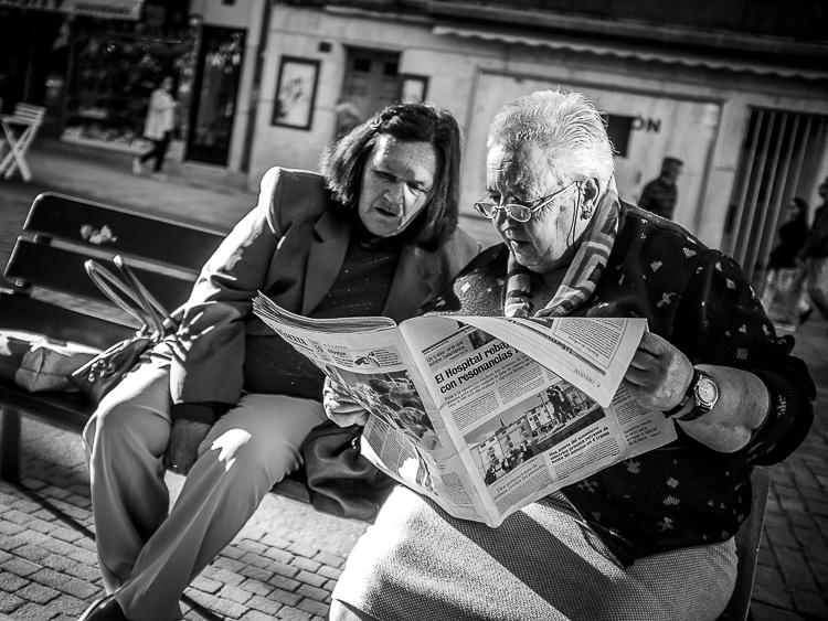 Pareja leyendo el periódico en el parque