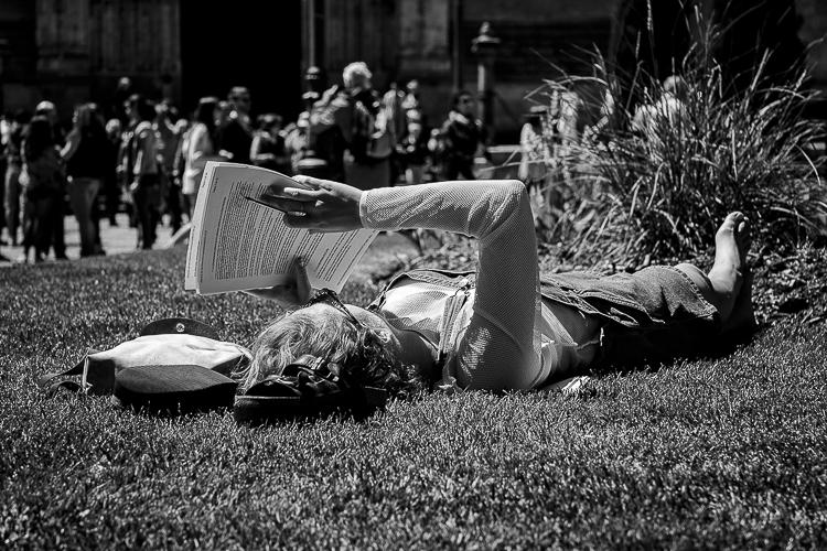 Chica leyendo en un parque tumbada