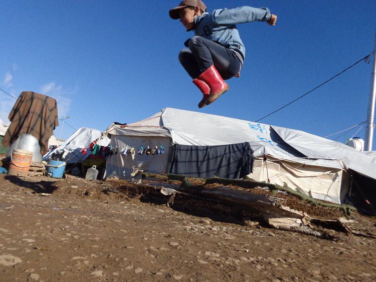 Niño refugiado saltando en el campamento