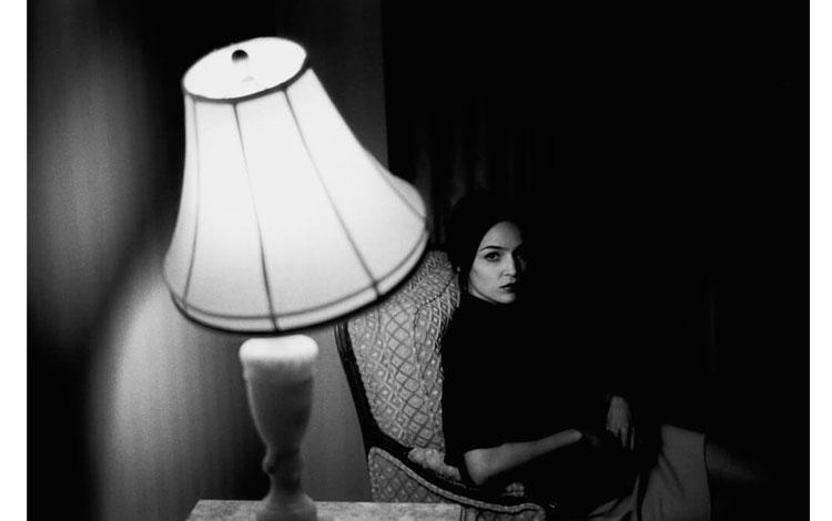 chica sentada con la luz de una lámpara