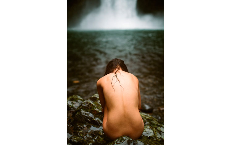Chica desnuda frente a una cascada
