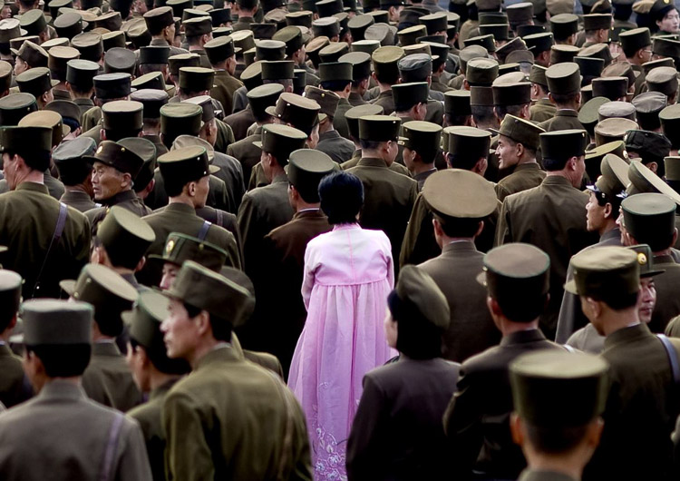 Mujer vestida de rosa entre militares