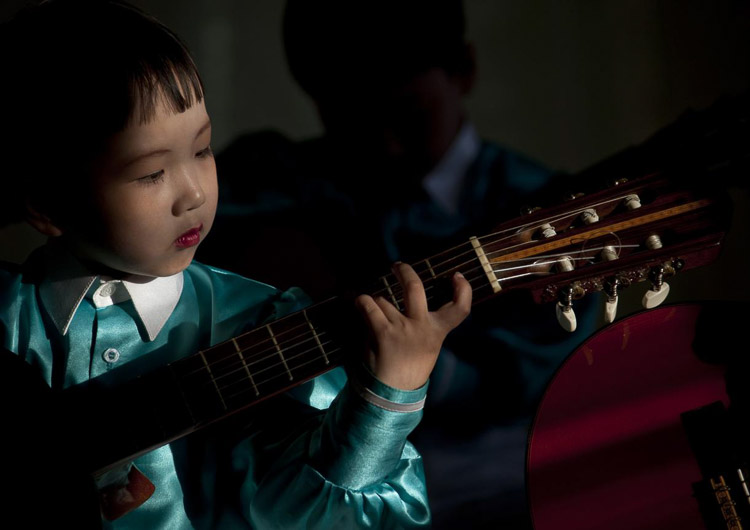Niña norcoreana tocando instrumento