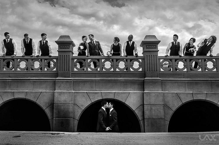 Novios debajo de un puente con invitados