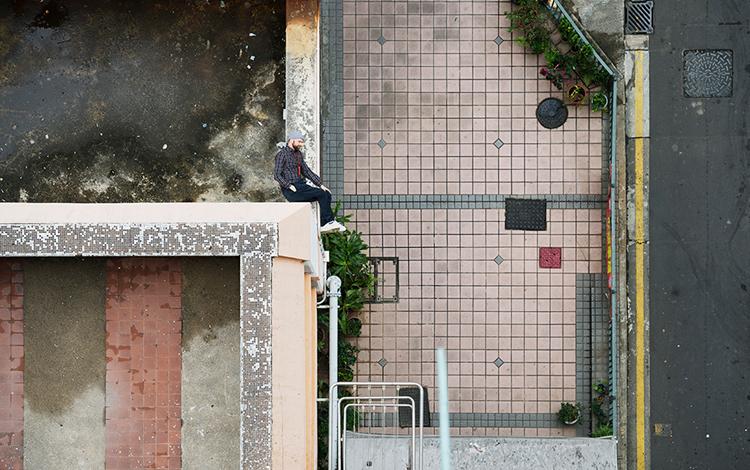 Hombre sentado sobre edificio