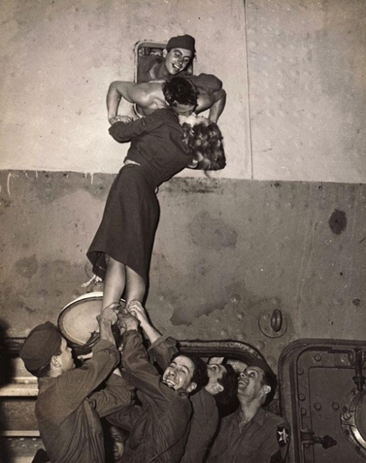 Una mujer subida por hombres besa a otro que se asoma desde un barco