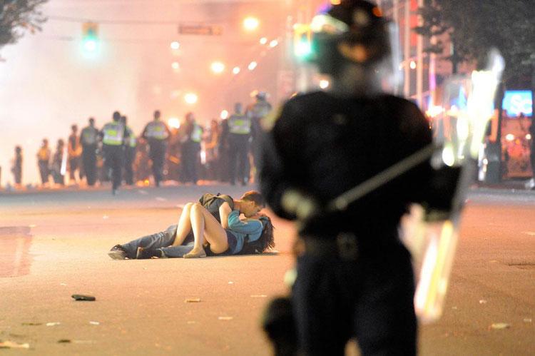 Dos jóvenes se besan tirados en el suelo en medio de unos disturbios