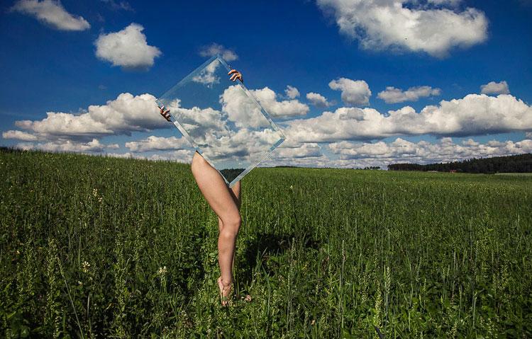 Mujer en el campo sujetando un expejo que la cubre